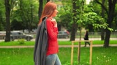 Confident Red Haired Girl In trendy Clothes Goes On Street Park Path. Having Dark Cardigan On Shoulder. Smiling.