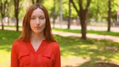 若々しい : Beautiful Lady Posing on Summer Nature. Young Woman Wearing Red Blouse. Female Model in Sunny Park. 動画素材