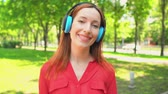 Cute Red Haired Girl Spending Time In Green Park. Wearing Headphones. Smiling And Moving By Music. Free Time Concept.