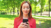 пользователь : Young Business Woman Texting Messages in Smartphone. Female Spends Time on Nature in Beautiful Summer Park.