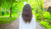 dinlenmek : back view brunette woman walking in the park along green trees turn to the camera friendly smiling to the viewers
