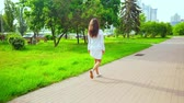 atriz : back view brunette wearing white dress and hoodie walking in modern town with green nature casual female going by the green trees on the background heavy traffic and city scape