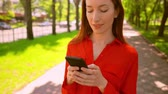 barátságos : elegant caucasian woman holding mobile chatting online female in red shirt standing on the street nature summer background Stock mozgókép