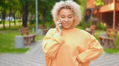 呼び出し : african american happy girl talking with friend by phone walks in summer city with green nature and cityscape background 動画素材