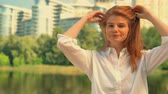 楽しんで : young caucasian woman with red hair looking camera cheerful female in white shirt posing outdoors background cityscape lake and green trees
