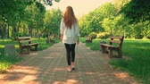 freizeitpark : back view caucasian young woman walking turn to the camera laughing female with red hair in casual jeans and white shirt in city with green nature