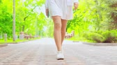 bacaklar : details female in white dress and sneakers walks holding smartphone summer background outdoors Stok Video