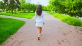 brunettes : caucasian girl wearing white dress enjoy her walk in summer city turn to the camera have fun smiling nature background with green trees Stock Footage