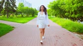 時尚 : young woman have fun walks in summer city with green outdoors background and cityscape wearing white dress and sneakers