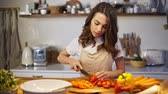 entediado : Young woman in apron getting tired while cooking in the kitchen Stock Footage