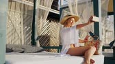 girlish : Gorgeous blonde woman 20s in summer straw hat have a rest on the beach take a selfie by mobile phone