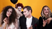 bruxa : Angry clown with air balloond looking at creepy characters with halloween make-up dancing isolated over orange