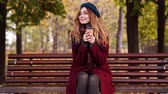 satisfeito : Pleased brunette woman in beret hat and coat drinking coffee while sitting on bench in park Stock Footage