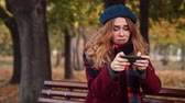 mládež : Concentrated brunette woman in beret hat and coat playing on smartphone while sitting on bench in park