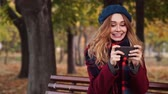 satisfeito : Happy brunette woman in beret hat and coat playing on smartphone while sitting on bench in park