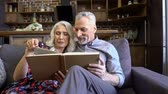 sofa : Pleased lovely elderly couple reading together while sitting together on sofa at home
