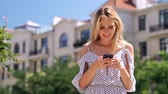 nőiesség : Happy blondy woman in dress using smartphone while standing at park