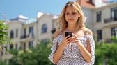 vay : Surprised blondy woman in dress using smartphone and upset while standing at park