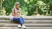 step by step video : Smiling pretty students woman using smartphone with cup of coffee while sitting on stairs outdoors