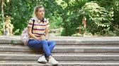 copos : Calm pretty students woman waiting someone with cup of coffee while sitting on stairs outdoors