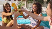 quatro pessoas : Group of Cheerful Beauty women friends in swimsuits drinking cocktails while relaxing together on lounge chairs near the swimming pool