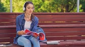 dergi : Pleased brunette woman using smartphone and listenning music while sitting on bench in park