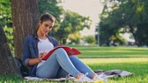 rivista : Smiling brunette woman reading magazine and writing something while sitting near the tree on grass in park