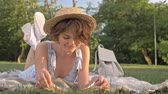 strohhut : Cute young woman reading book and smiling looking at the camera while lying on a plaid in the park Stock Footage