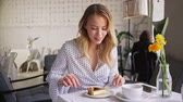 halenka : Pretty excited young blonde woman drinking a cup of coffee and eating cheesecake while sitting in cafe