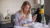 bluz : Smiling beautiful young blonde woman eating cheesecake and looking at smartphone while sitting in cafe Stok Video