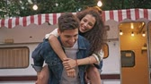 meeliften : Happy young lovely couple piggybacking while having fun near trailer in the park