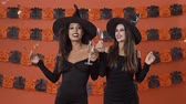 confete : Cute smiling young witch women in black halloween costumes dancing under confetti and clinking glasses with champagne over orange pumpkin wall Stock Footage