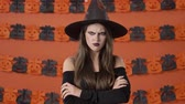 čarodějnice : Displeased young witch woman in black halloween costume taking offense at someone and crossing her arms while looking at the camera over orange pumpkin wall