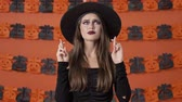 calabaza : Attractive young witch woman in black halloween costume crossing her fingers with hope and asking for something while looking up over orange pumpkin wall