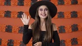 adios : Beautiful happy young witch woman in black halloween costume smiling and waving with hand to the camera over orange pumpkin wall