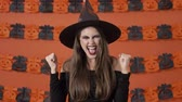 kiabálás : Cheerful pretty young witch woman in black halloween costume making winner gesture with hands over orange pumpkin wall Stock mozgókép