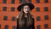 sertés : Displeased beautiful young witch woman in black halloween costume getting angry and taking offense at someone over orange pumpkin wall