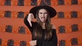 frightening : Displeased pretty young witch woman in black halloween costume making thumb down gesture and showing her tongue over orange pumpkin wall