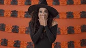 czarodziej : Shocked pretty young witch woman in black halloween costume covering her mouth with hands and shaking her head negatively over orange pumpkin wall Wideo