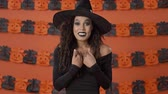 chi : Surprised cheerful young witch woman in black halloween costume covering her mouth with hands and asking who, me over orange pumpkin wall