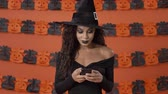 verbinding maken : Concentrated calm young witch woman in black halloween costume chatting on smartphone over orange pumpkin wall Stockvideo