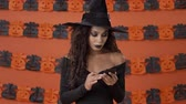 czarodziej : Serious attractive young witch woman in black halloween costume becoming shocked and confused while using smartphone over orange pumpkin wall Wideo