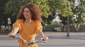lovaglás : Cheerful young redhead curly woman smiling while riding bicycle outdoors in the park