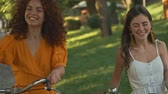 Happy beautiful young girls friends smiling and laughing while walking with bicycles outdoors in the park