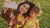 arabisch : Smiling indian woman making selfie on smartphone with her pleased child girl which eating lollipop in park outdoors