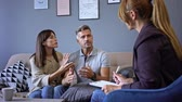 érv : Unhappy couple man and woman having conversation with psychologist on therapy session in room