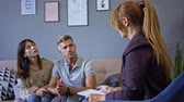 érv : Annoyed couple man and woman having conversation with psychologist on therapy session in room