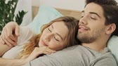 sonhar : Happy couple man and woman lying together in bed and dreaming