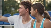 corte : Smiling curly male tennis player making selfie and having rest together with his happy female opponent on tennis court