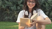 sedutor : Happy positive young girl wearing glasses is smiling while reading a book outside in the city park